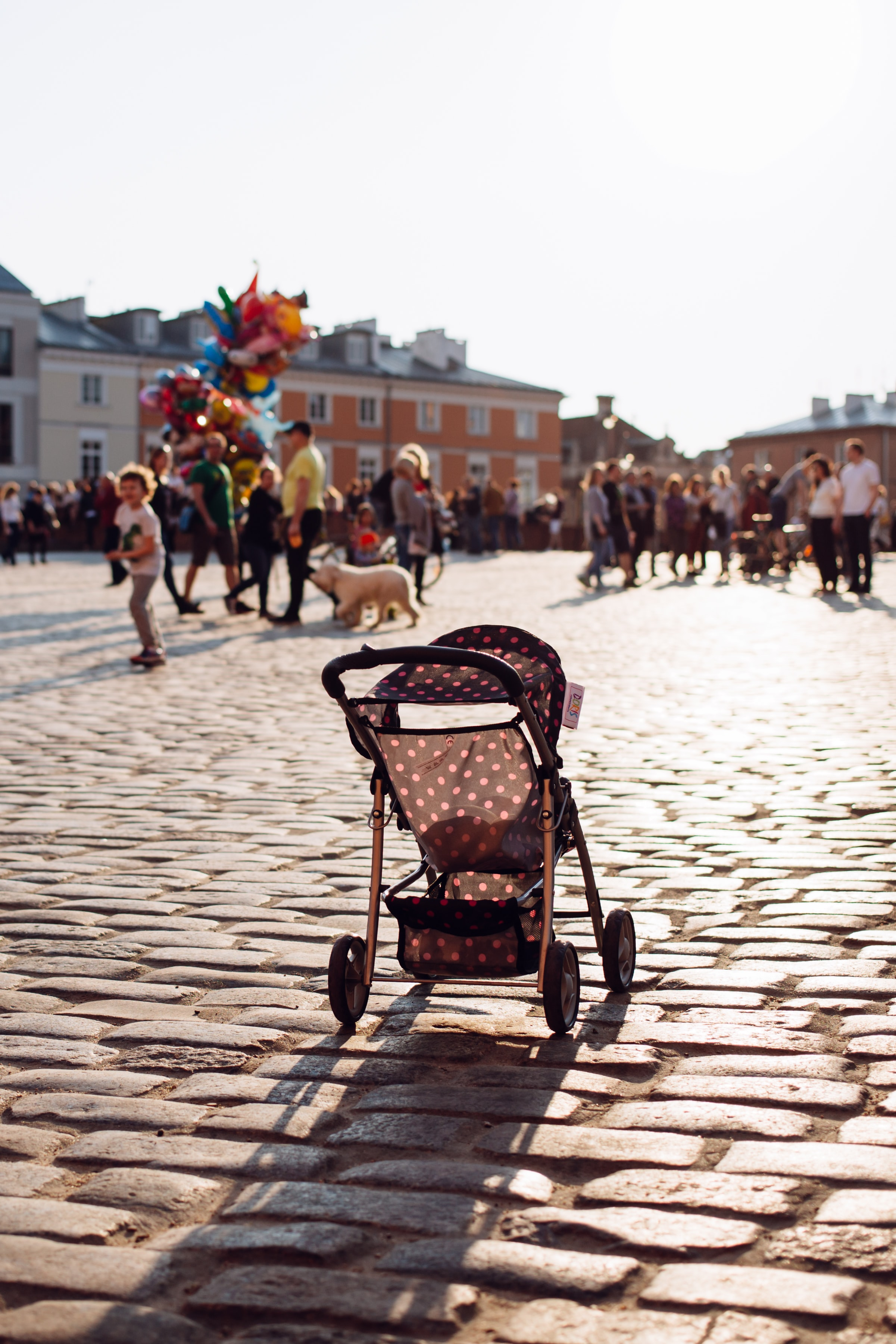 gray and white polka-dot stroller in the middle of street