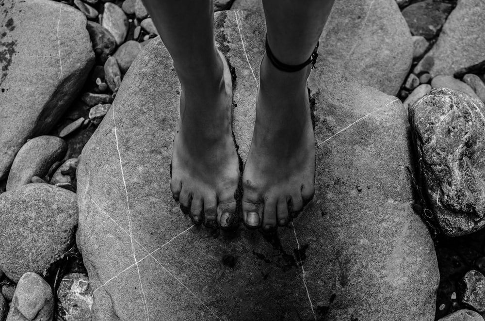 grayscale photography of person standing on rock