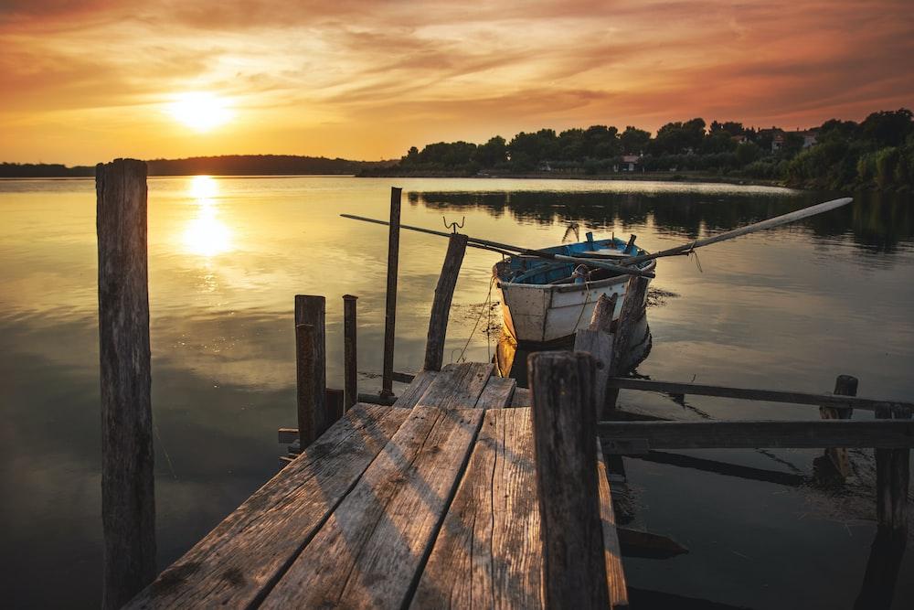 white wooden boat near wooden dock
