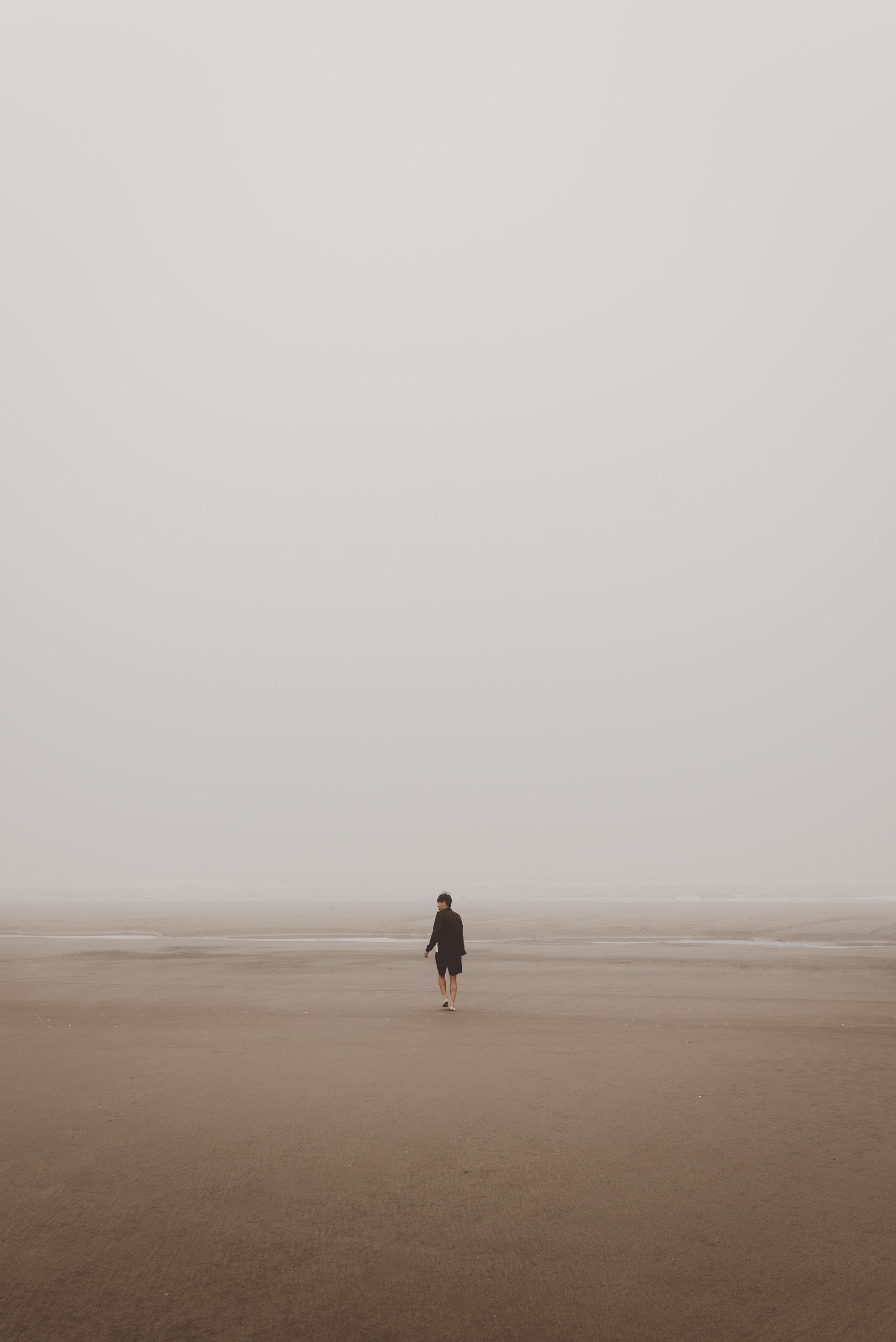 man standing on brown sand