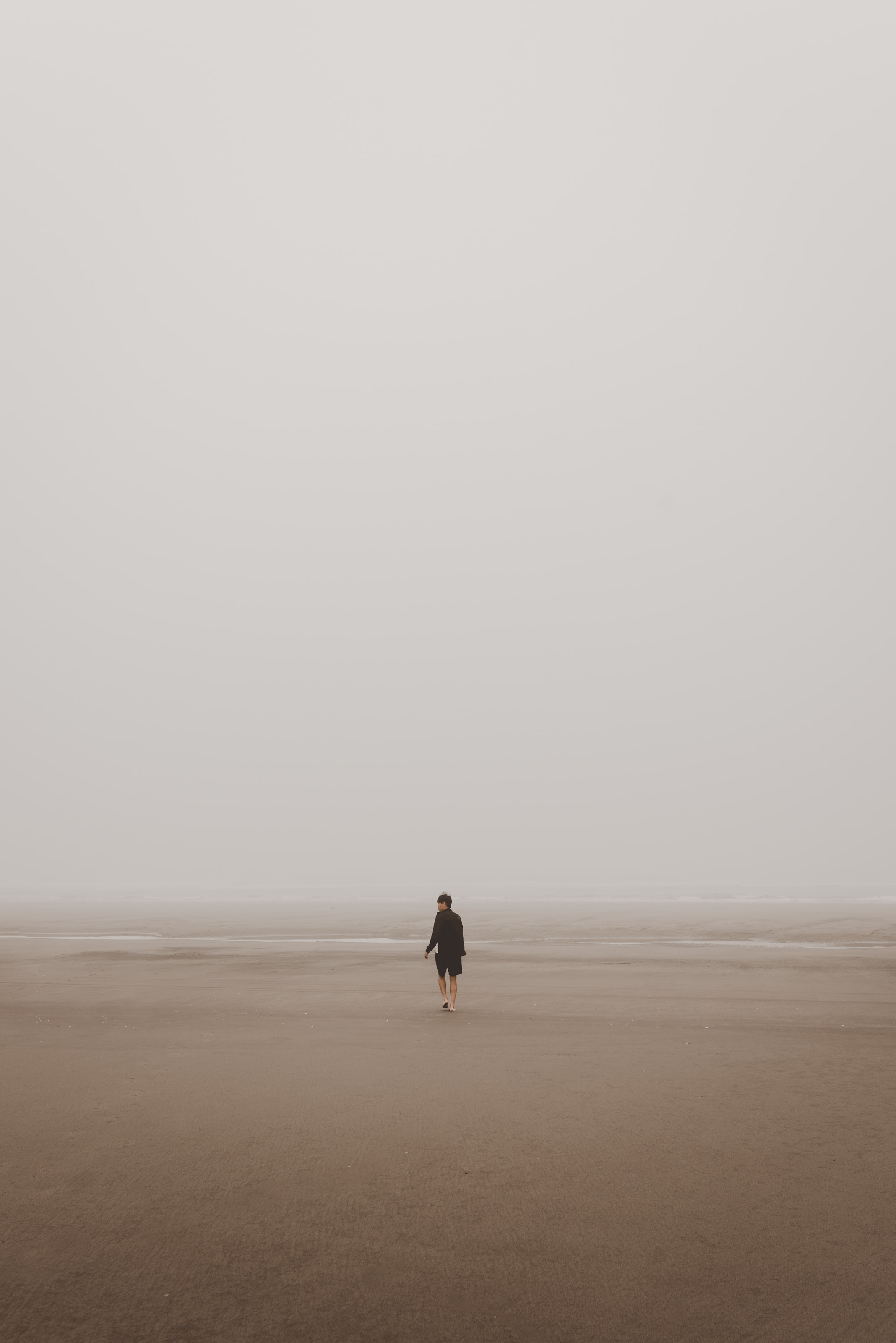 man standing on brown sand