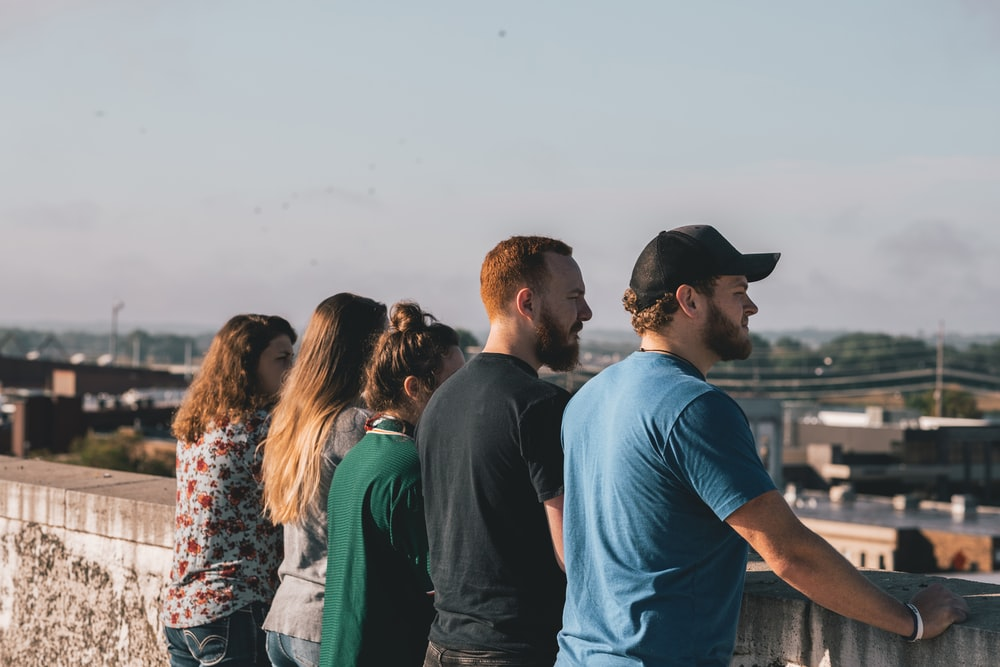 four people leaning on concrete rails