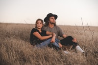 woman and man sitting on wheat field