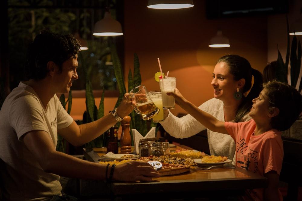 three people having a toast on table