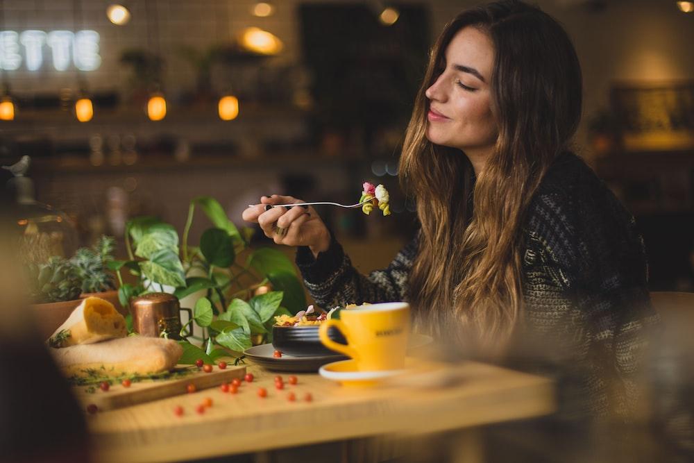 mujer con tenedor en la mesa delantera