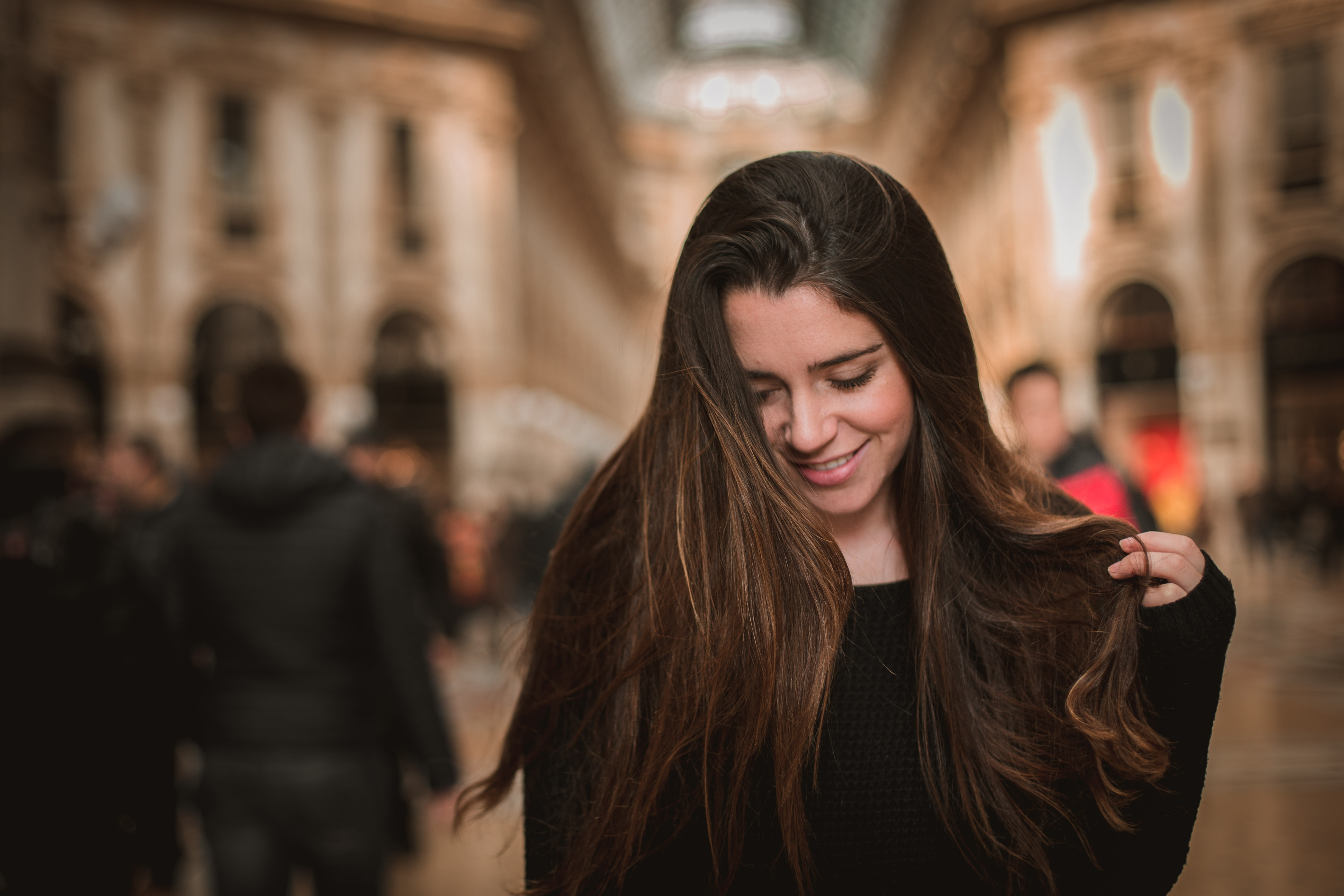 smiling woman holding her hair looking on ground