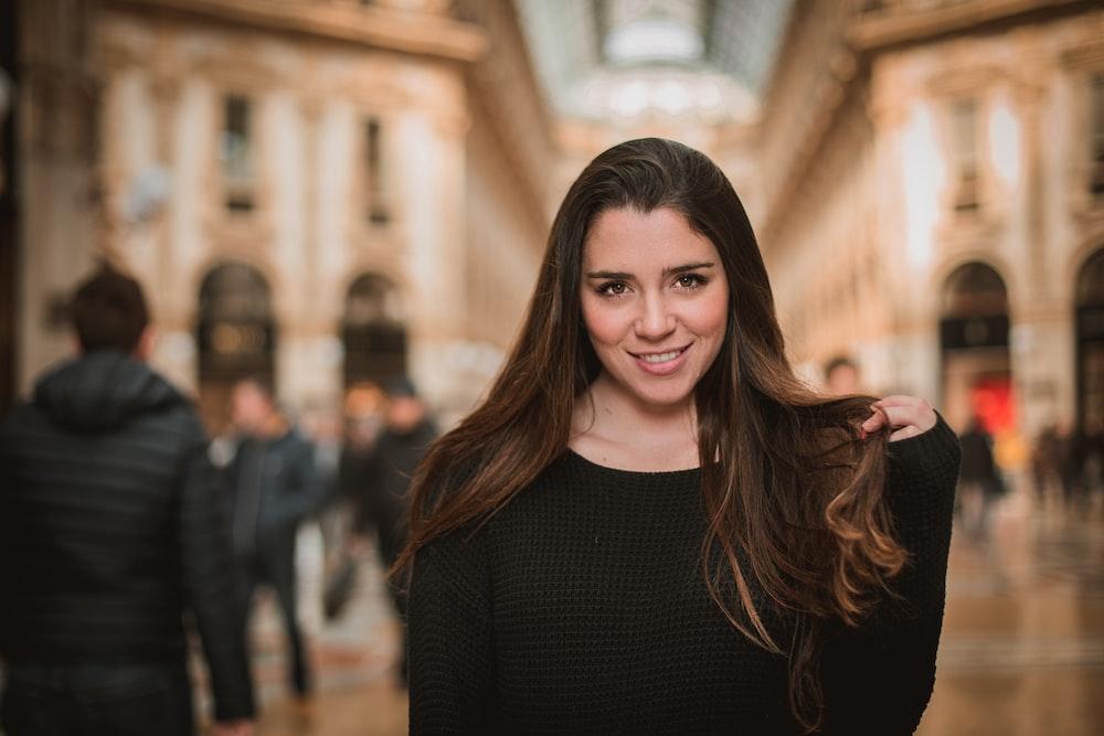 smiling woman in black long-sleeved top