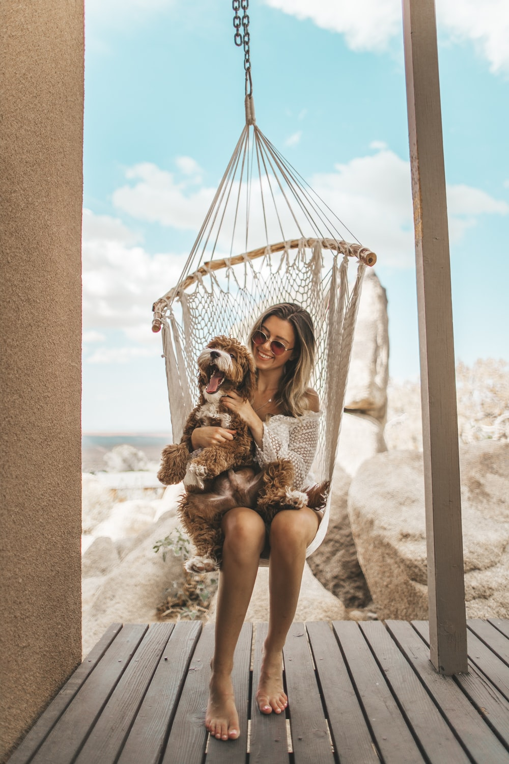 woman sitting on hammock with plush toy