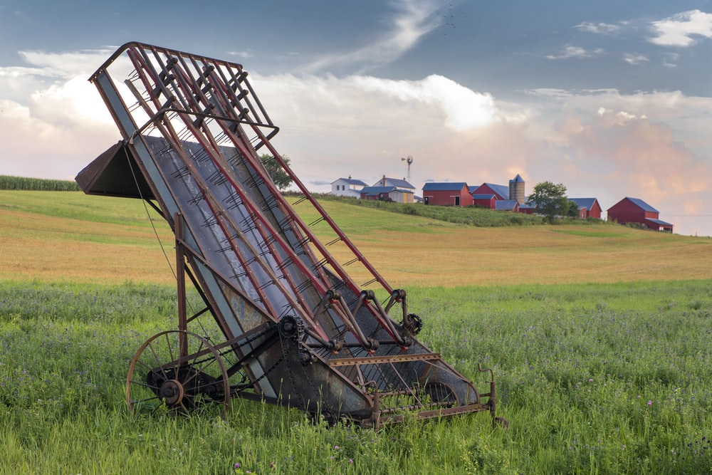 grey and red metal harvester machine on green field