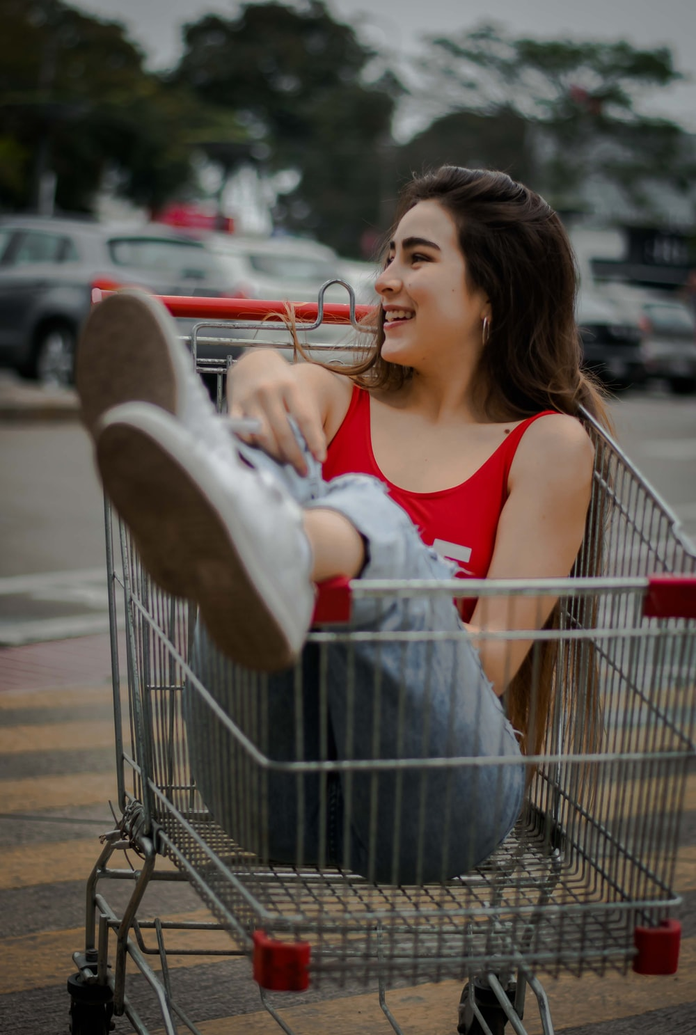 shallow focus photography of woman inside grocery cart trolley