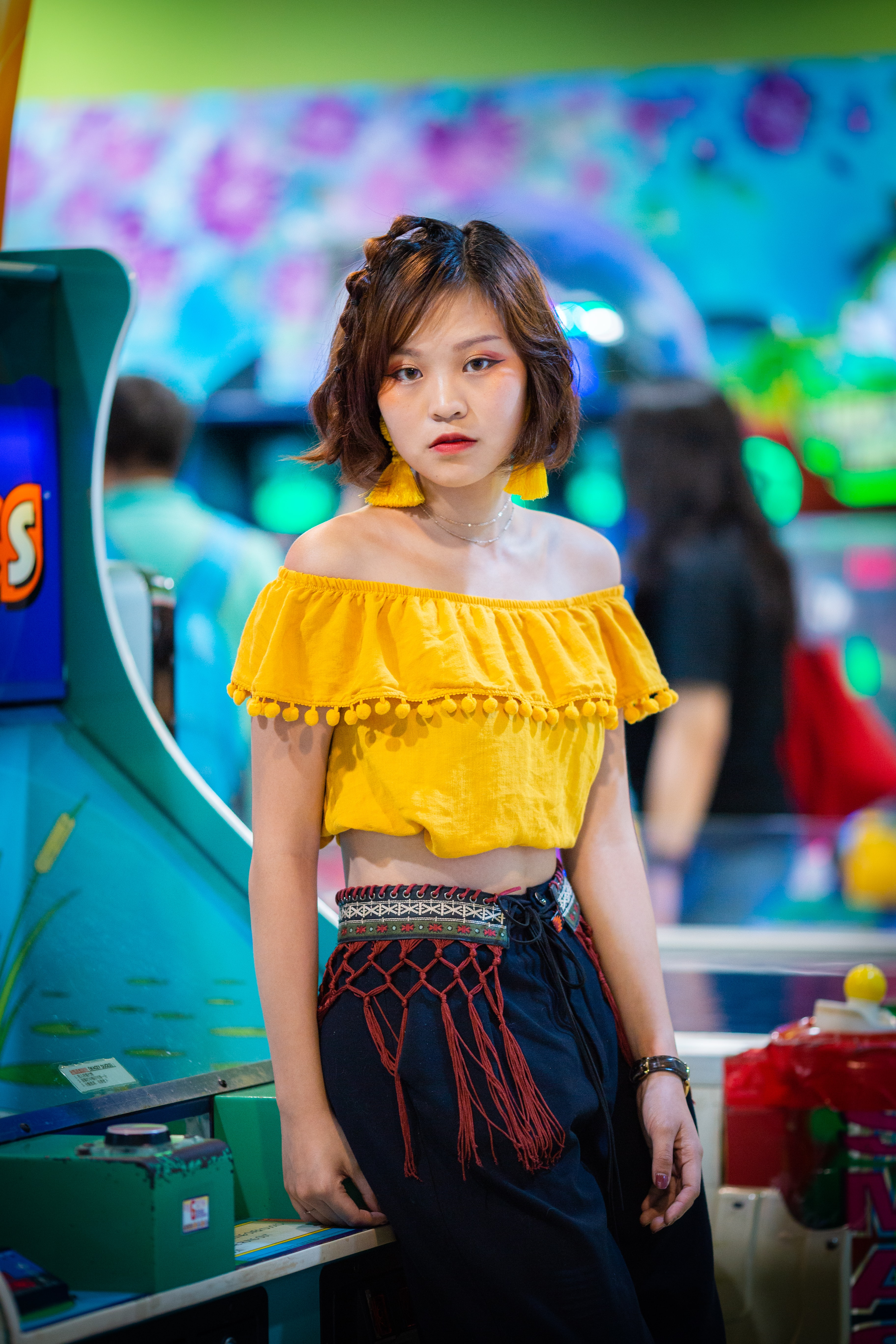 woman in yellow off-shoulder crop top sitting on green and blue arcade machine