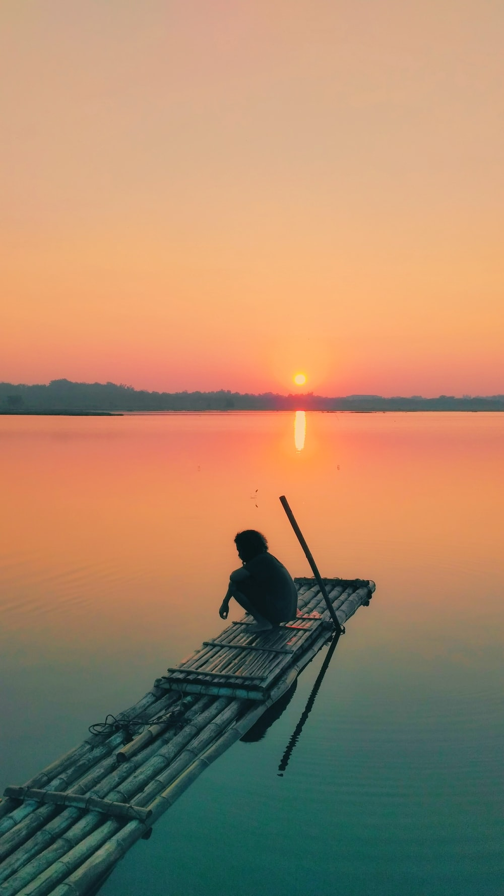 person sitting on bamboo boat