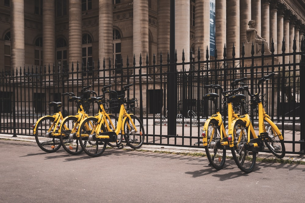 yellow bicycles beside black fence