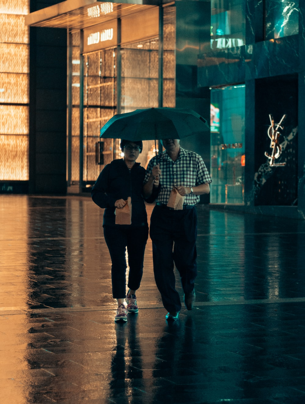 man and woman under same umbrella walking while holding paper bags
