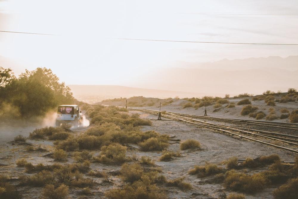 white car near train rail