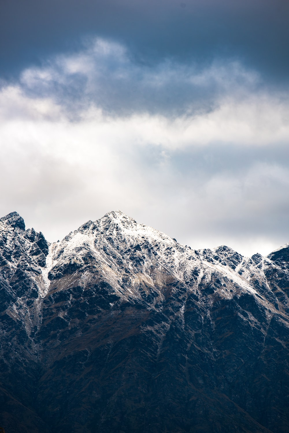 snow-capped mountain below cloudy sky