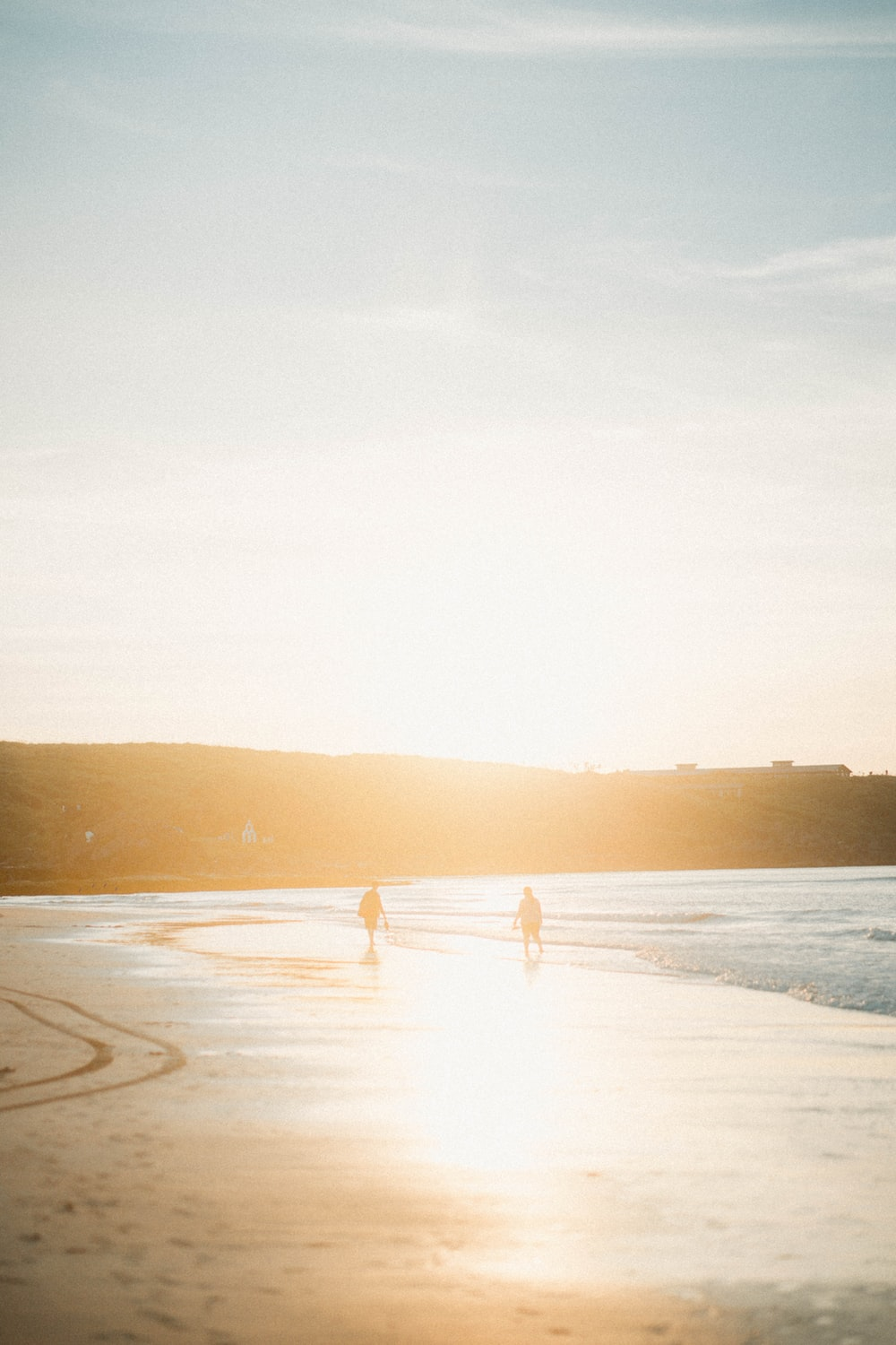 two person walking on seashore at golden hour