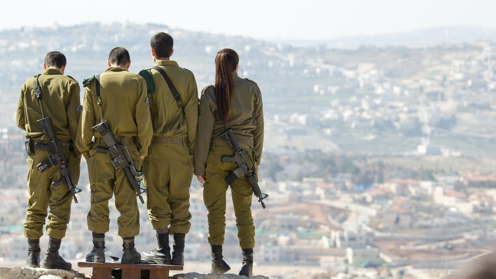 three men and one woman soldiers standing on rock during daytime
