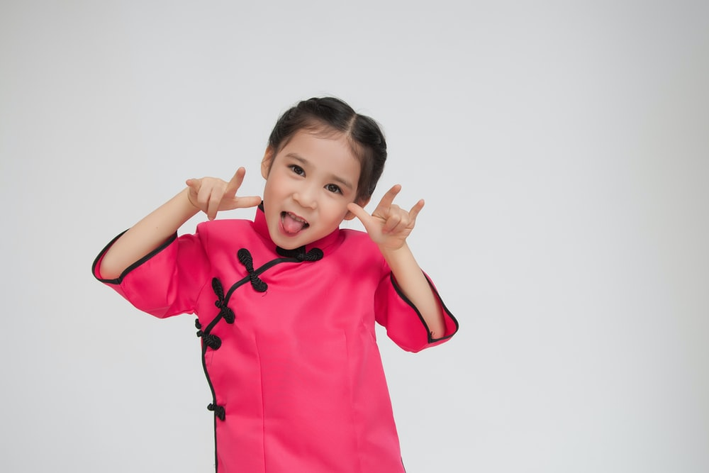 girl wearing pink dress sticking tongue out with hands gestures