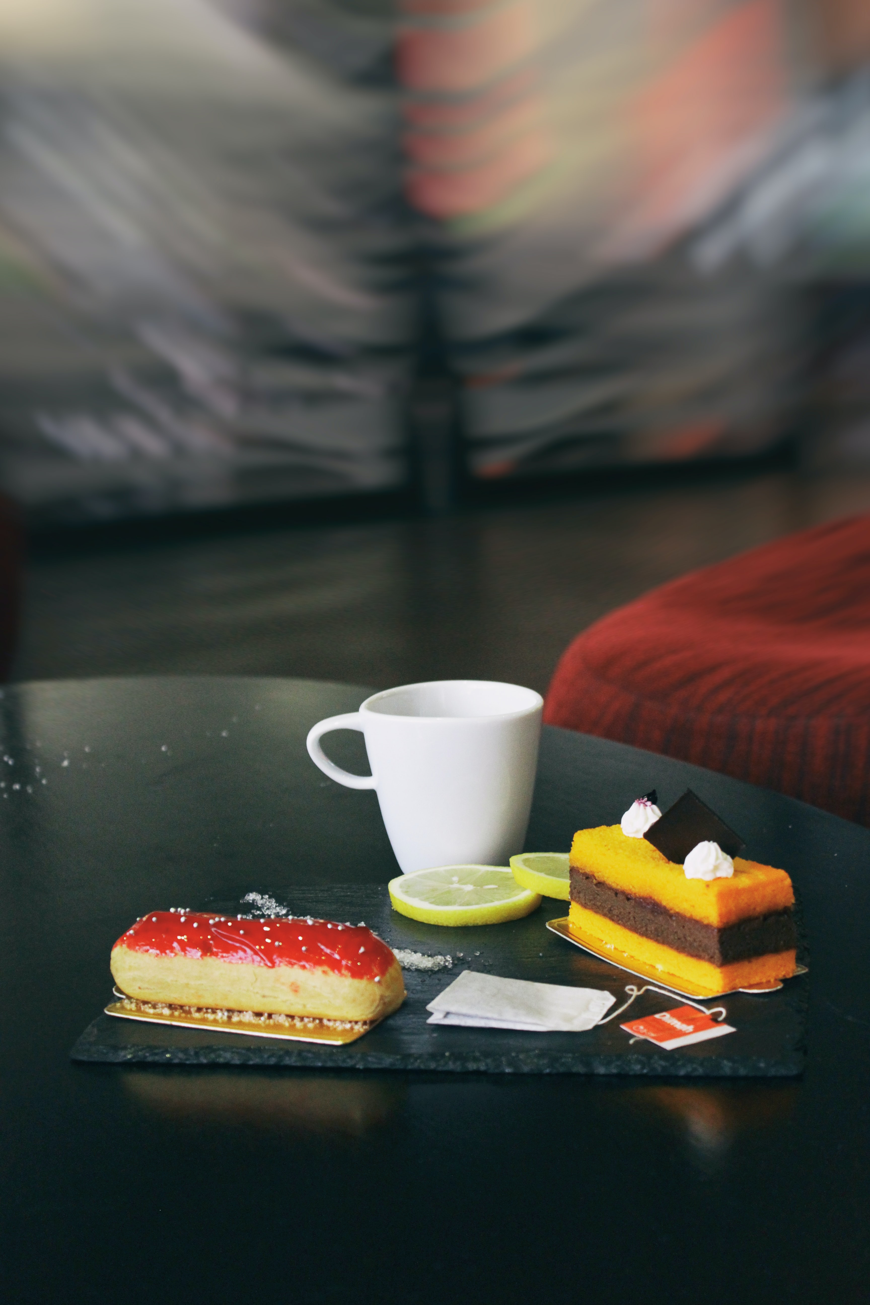 two piece of cakes and white mug on glass-top table