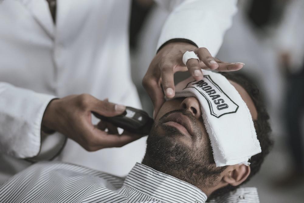 man shaving lying man