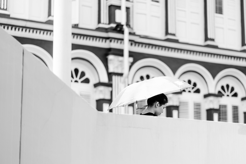 woman holding umbrella beside white concrete building