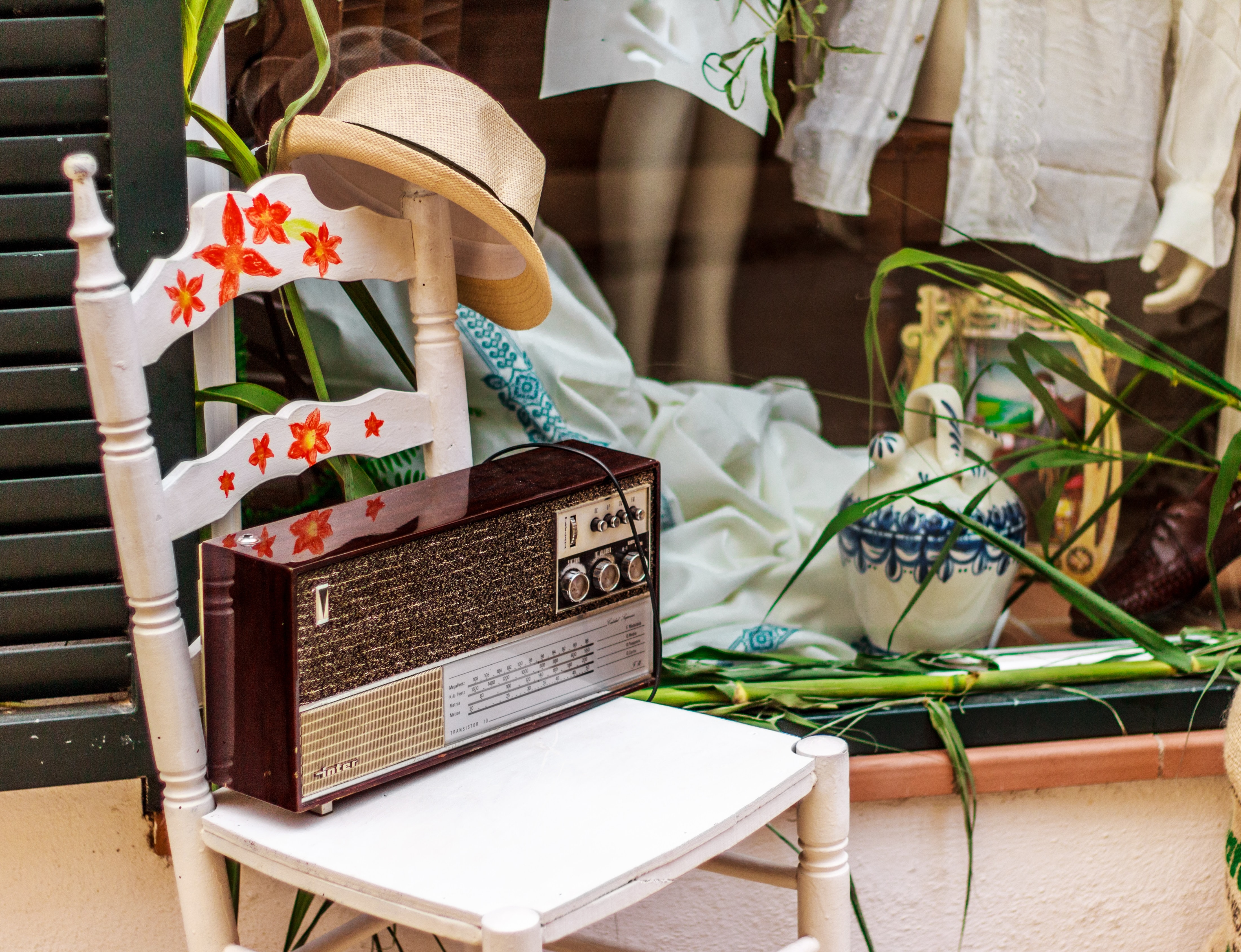brown radio on white wooden chair beside green plant