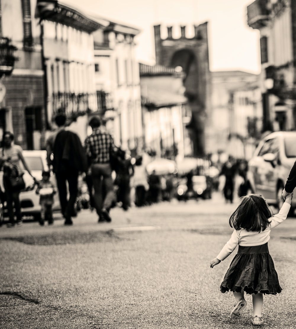 grayscale photography of child walking on pavement