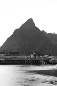 grayscale photography of houses below sea beside mountains at daytime