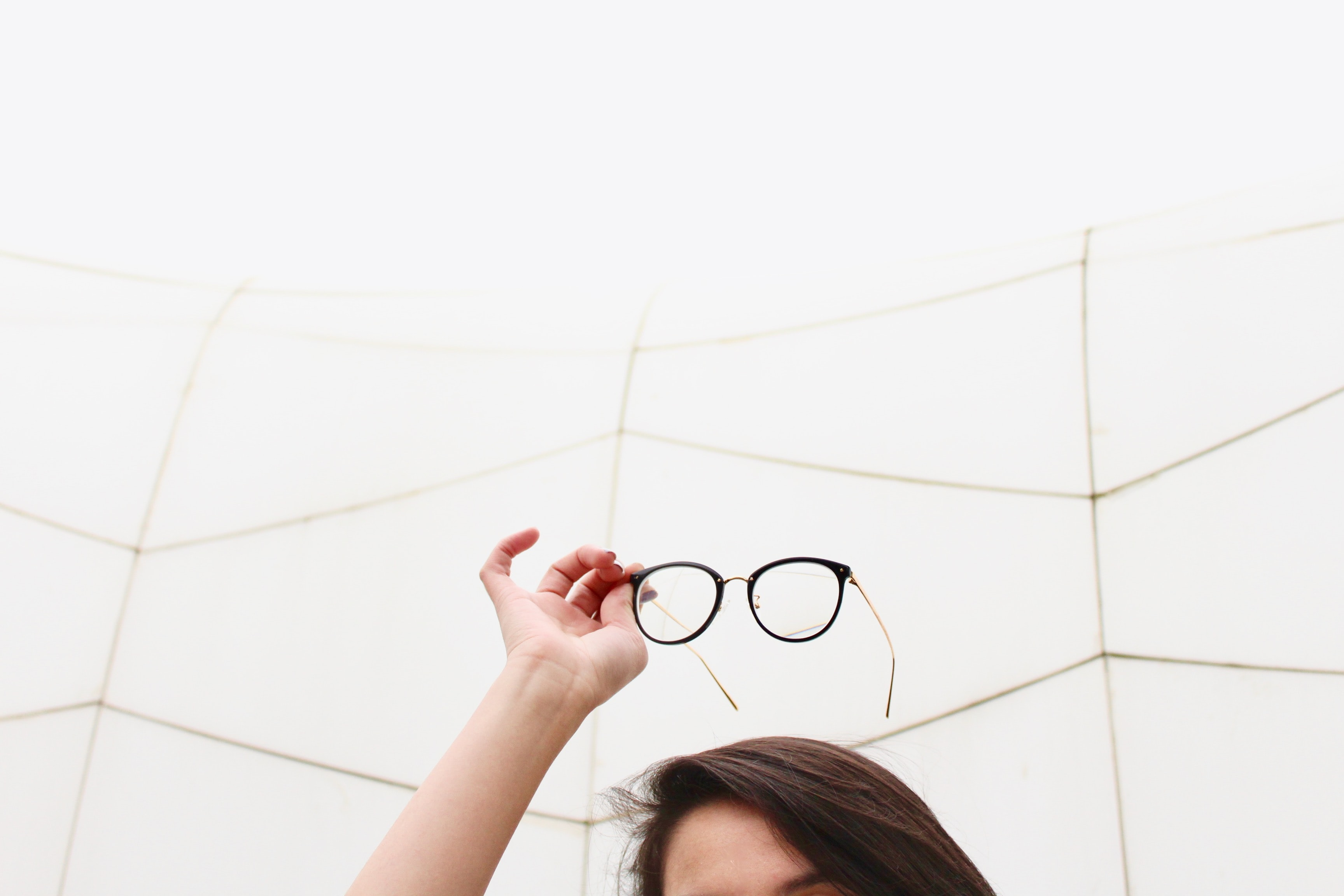 person holding black framed eyeglasses