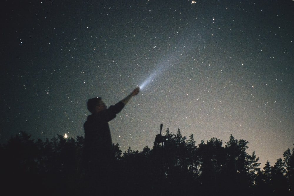 silhouette of man looking up during nighttime