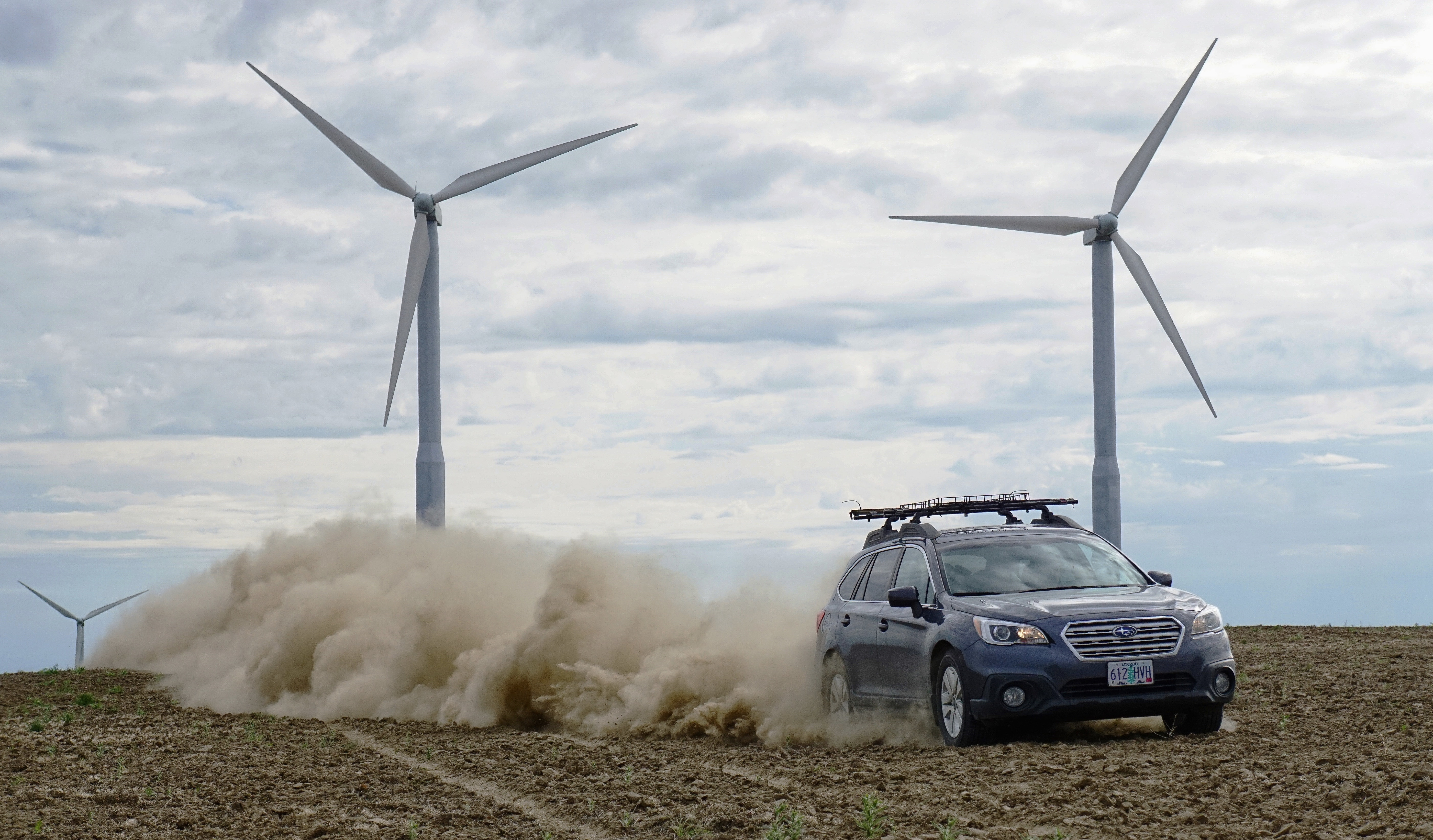 blue vehicle passing on gray wind turbines at daytime