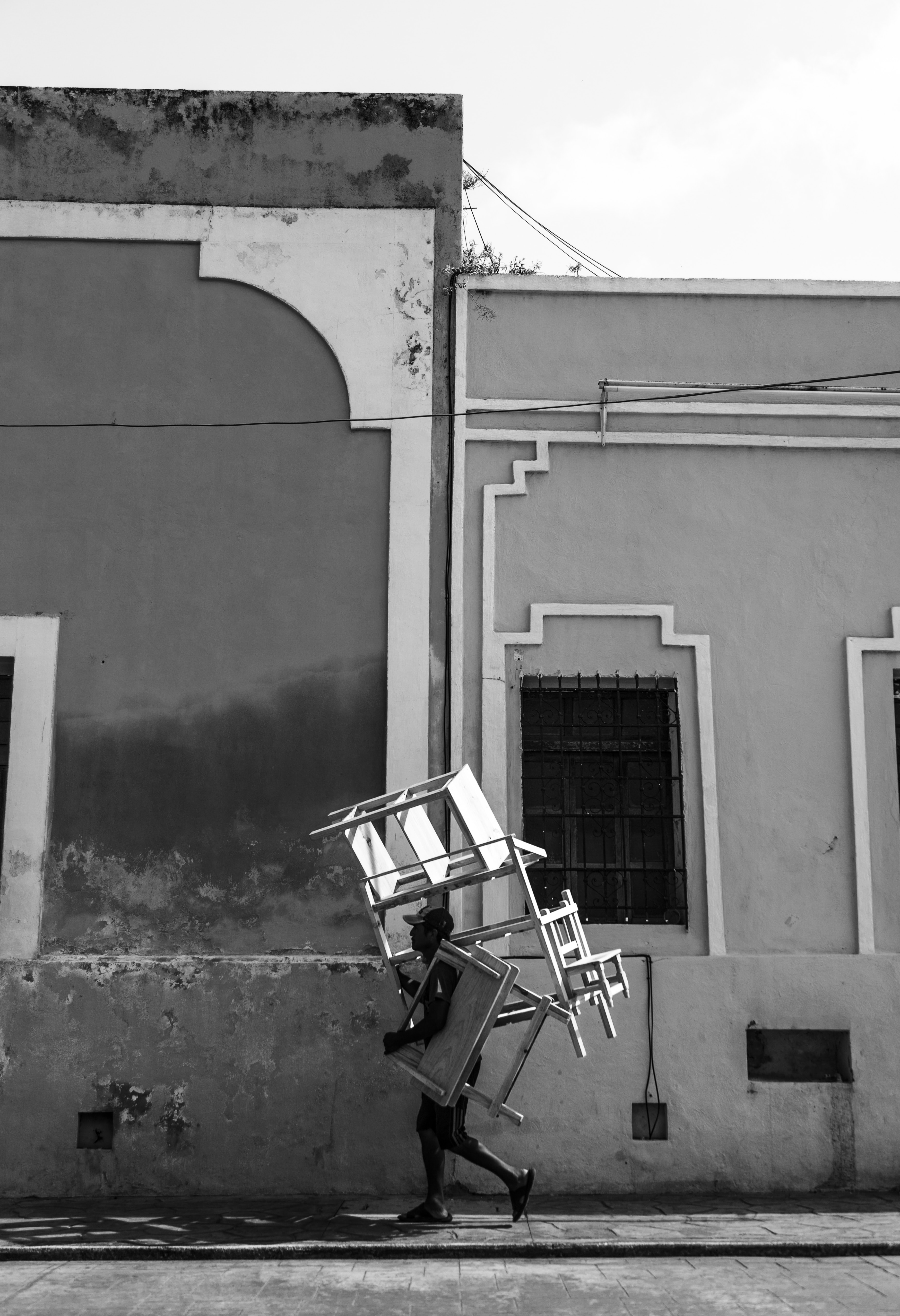 grayscale photography of person carrying furniture while walking near concrete house at daytime