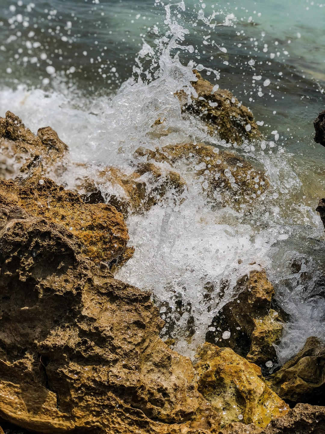 """I was enjoying a day at the beach and was lucky enough to be met by such beautiful rocks. They were screaming, """"Photograph me!"""" I complyed and captured this splash of water suspensed in the air, frozen in time."""