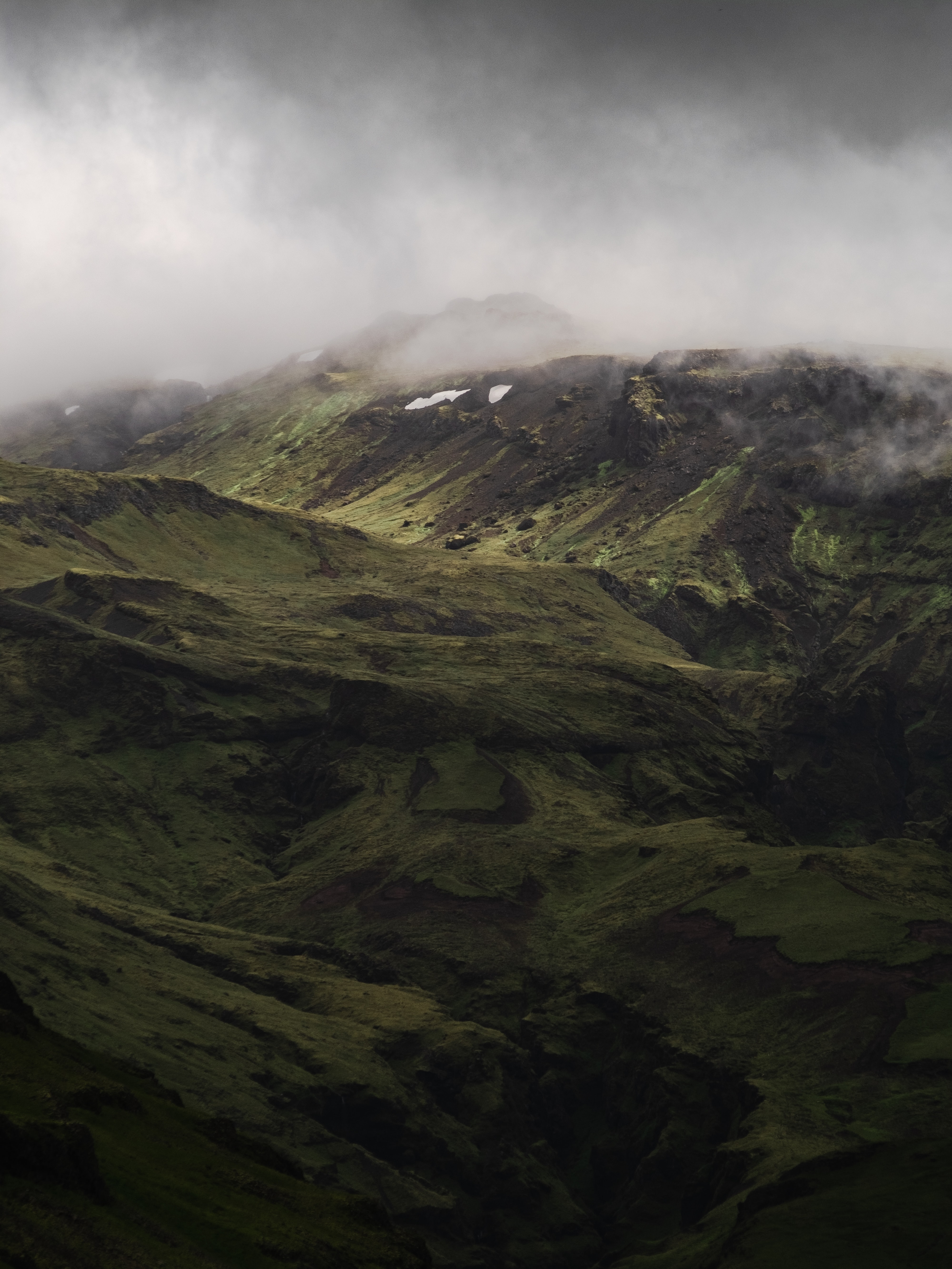 aerial photography of green mountain under cloudy sky