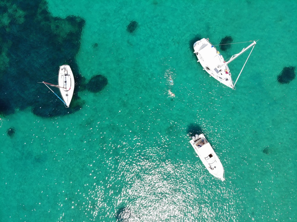 aerial view of three white boats on water
