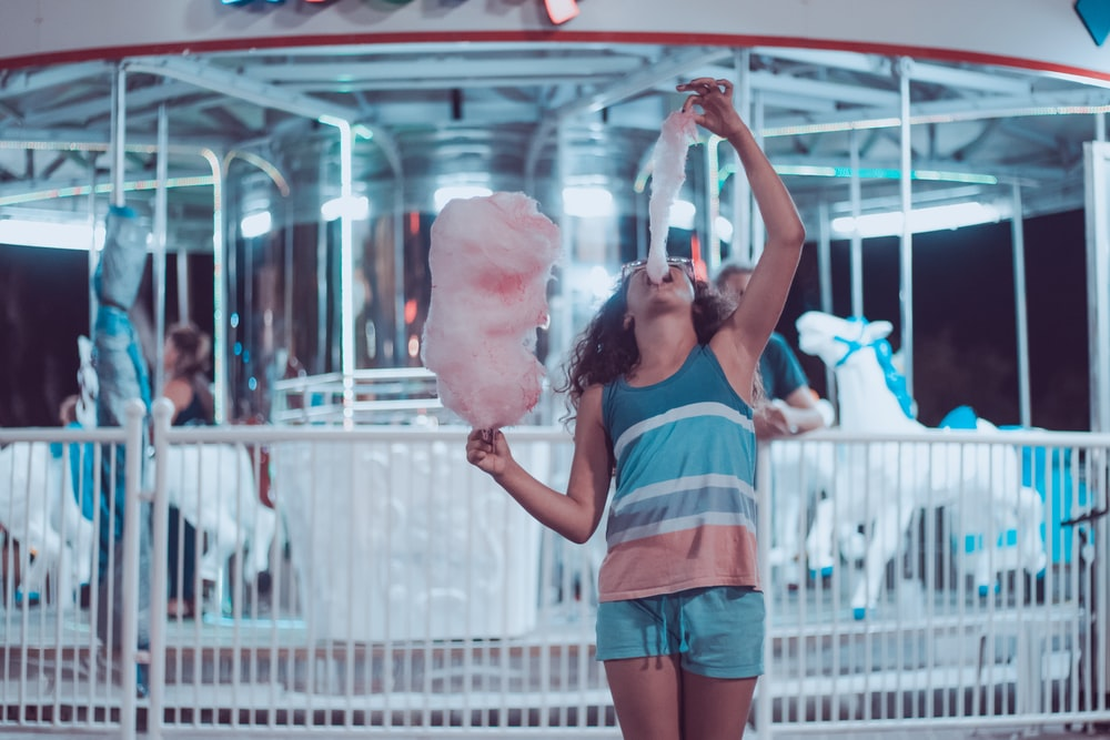 woman eating pink cotton candy beside carousel