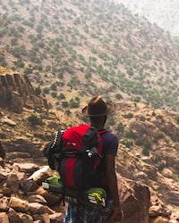 man hiking on brown mountain