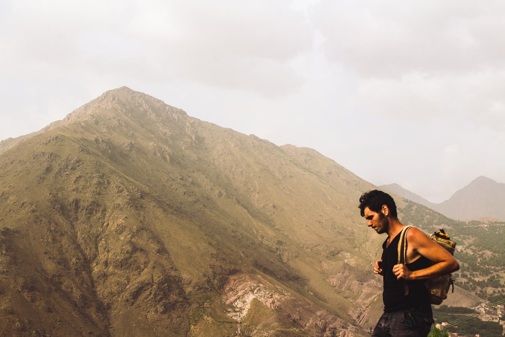 man carrying backpack standing near mountain