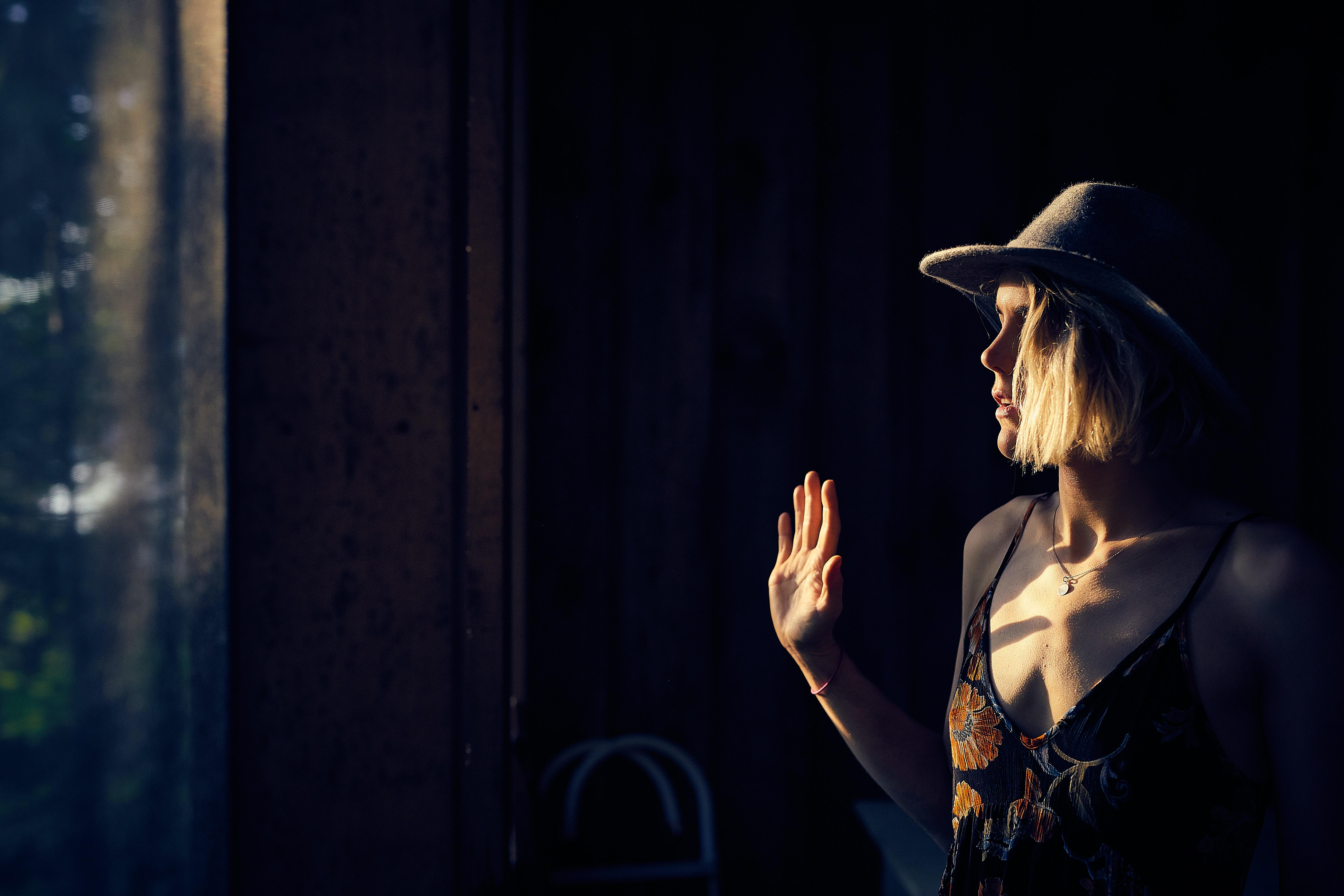 woman wearing brown floral spaghetti-strap dress standing beside window