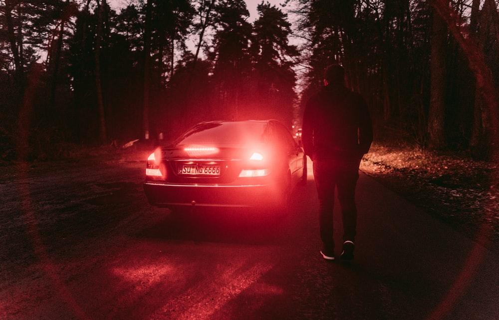 person standing near black car