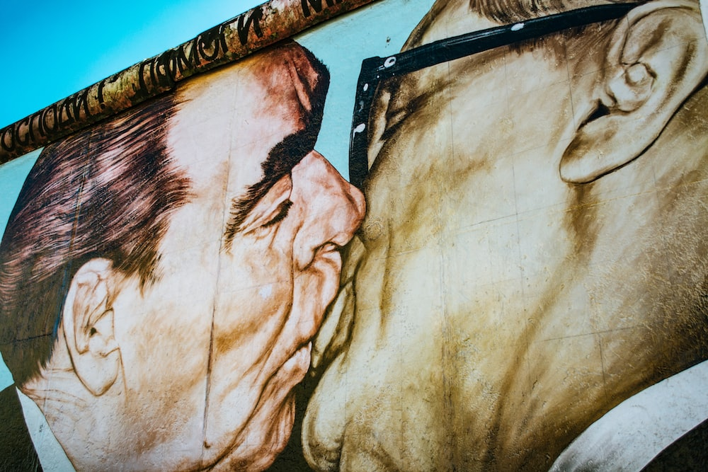man and woman kissing painting
