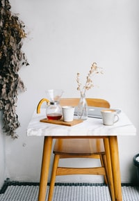 white ceramic mugs, clear glass pitcher and vase, and silver MacBook on top of white and brown table