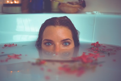 woman in bathtub with red flower petals floating on water