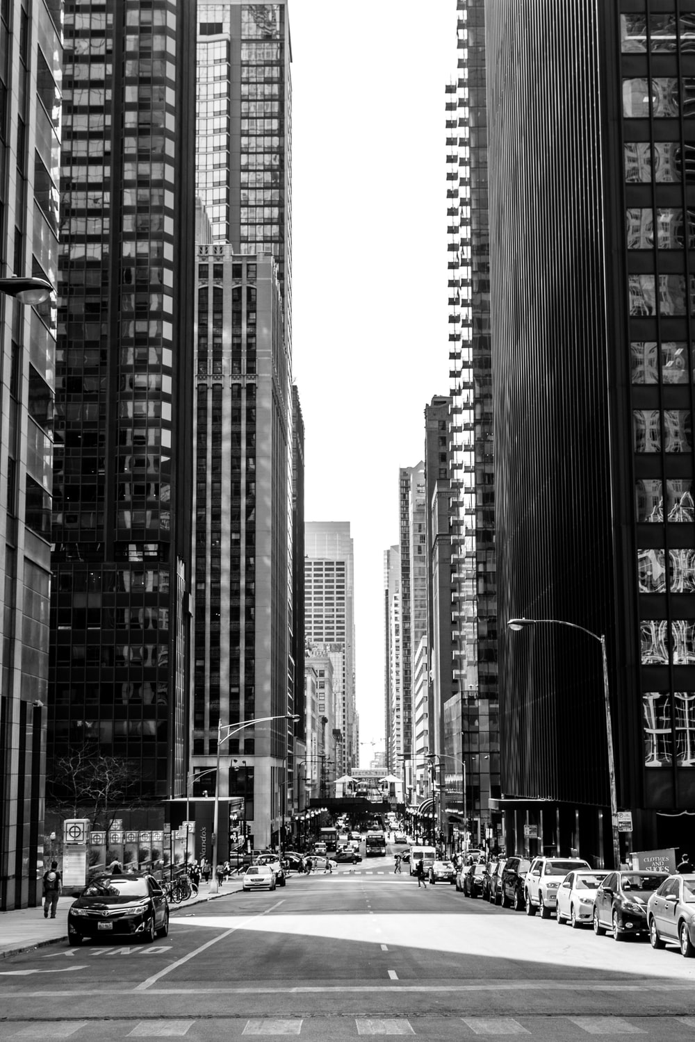 grayscale photo of road in between of tall buildings with vehicles