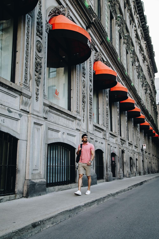 man wearing pink polo shirt walking beside gray concrete building