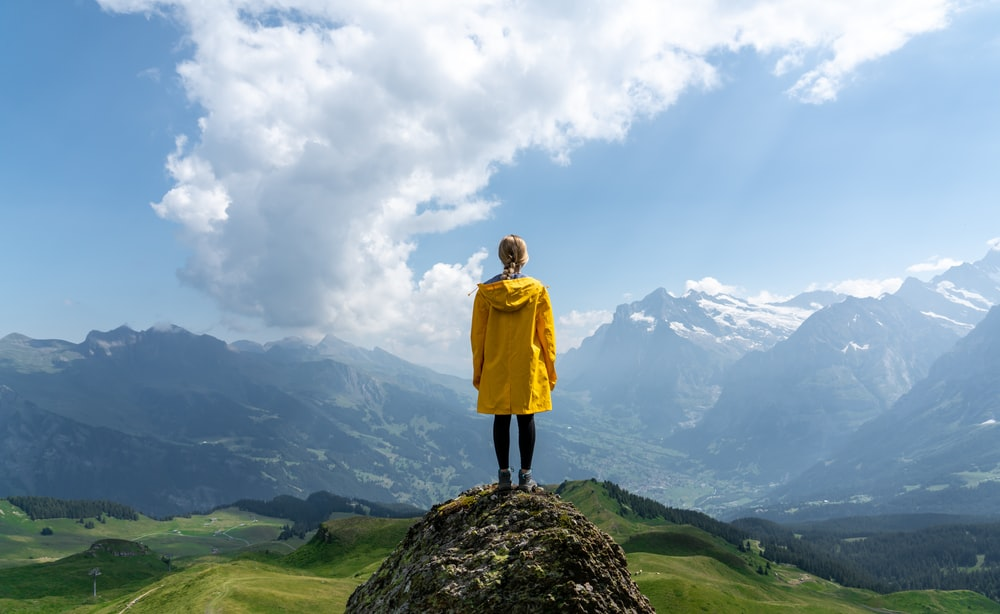 woman standing on rock in front of mountain during daytime