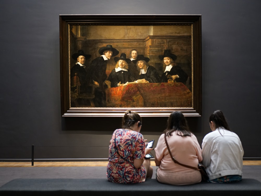 three women sitting on floor facing a painting mounted on wall