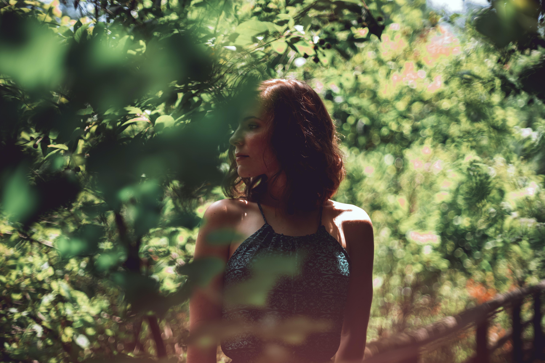 woman wearing halter top beside green tree