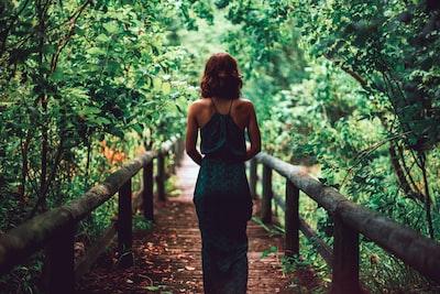 woman in black dress standing on bridge